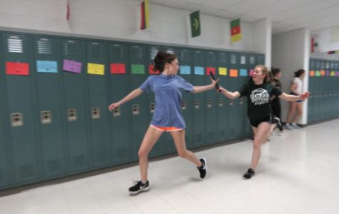Freshman Yasmine Khalaf grabs the baton from sophomore Ashlyn Duffee during practice.