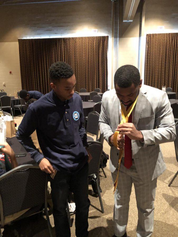 Junior Sigarrie Nettles watches Bears media coordinator Aaron Clark teach how to tie a tie.