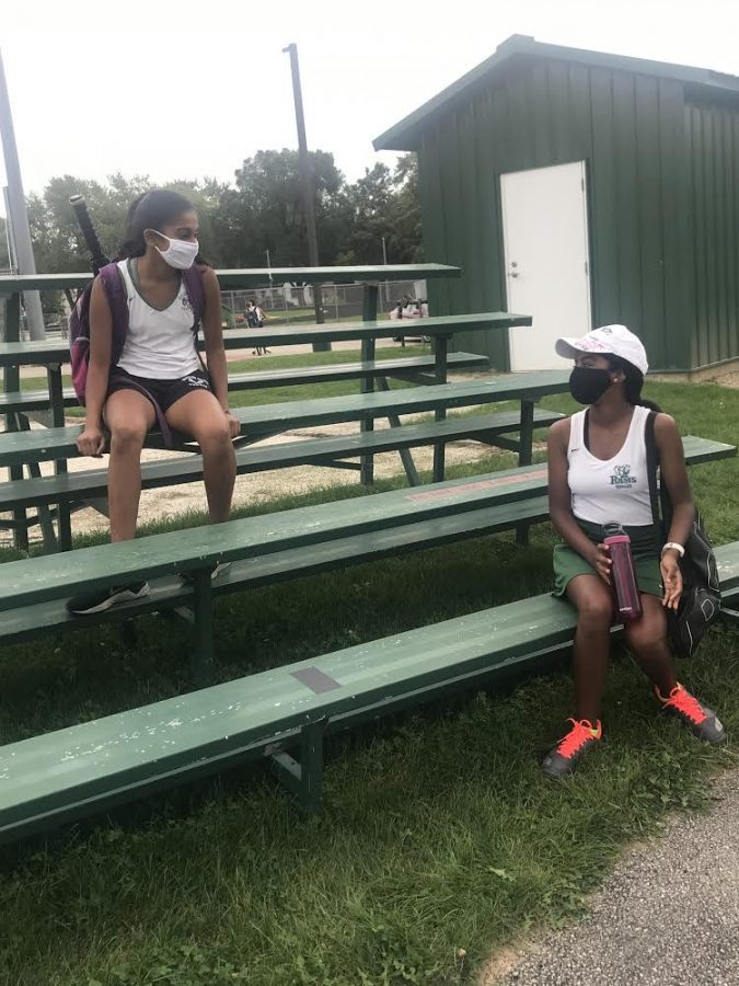 Thanya Sriselvakumar and Sudiksha Peramanu have a conversation after a tennis match, wearing face masks to keep each other safe. (Photo by Maia AlBarrak)