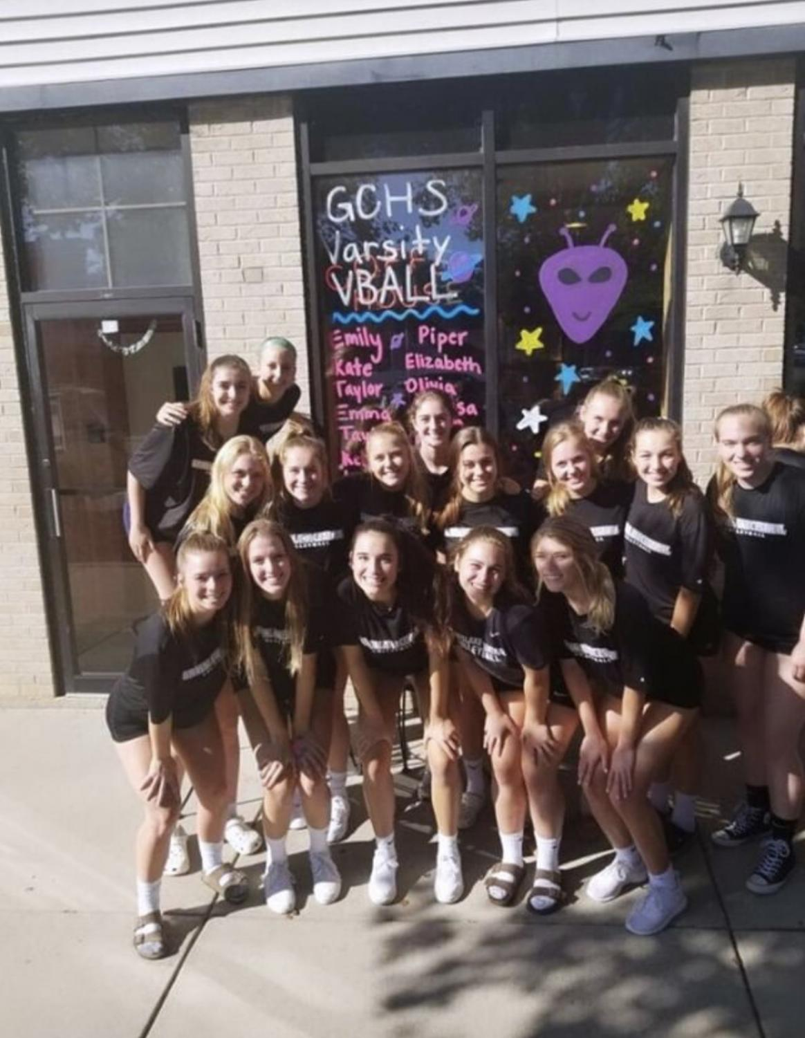 Volleyball team spends time together at the window painting event during their season.