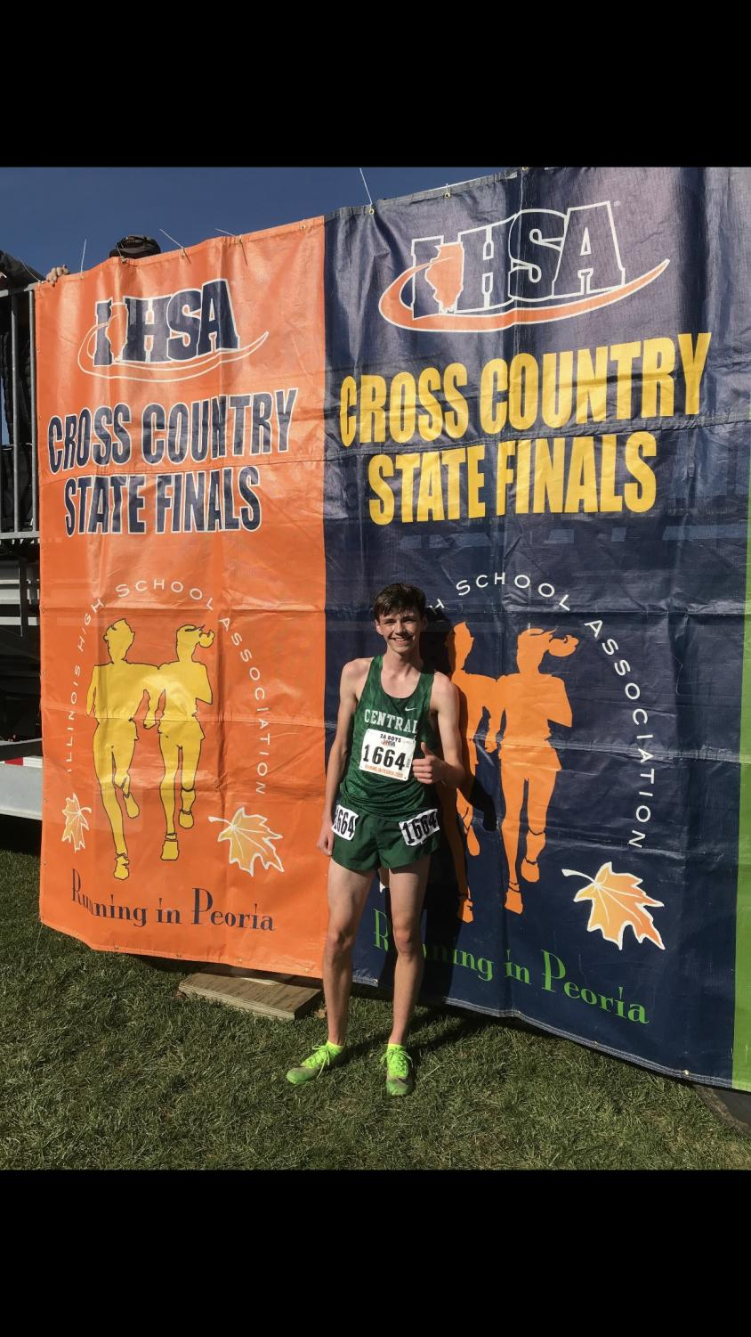 Craig Hundley smiles at the cross country state final banner.