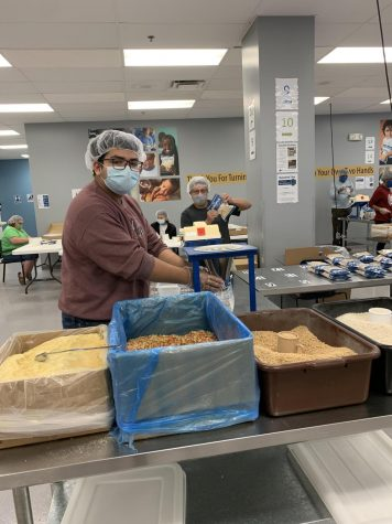 Senior Luis Martinez  is volunteering at Feed My Starving Children with masks and social distancing.