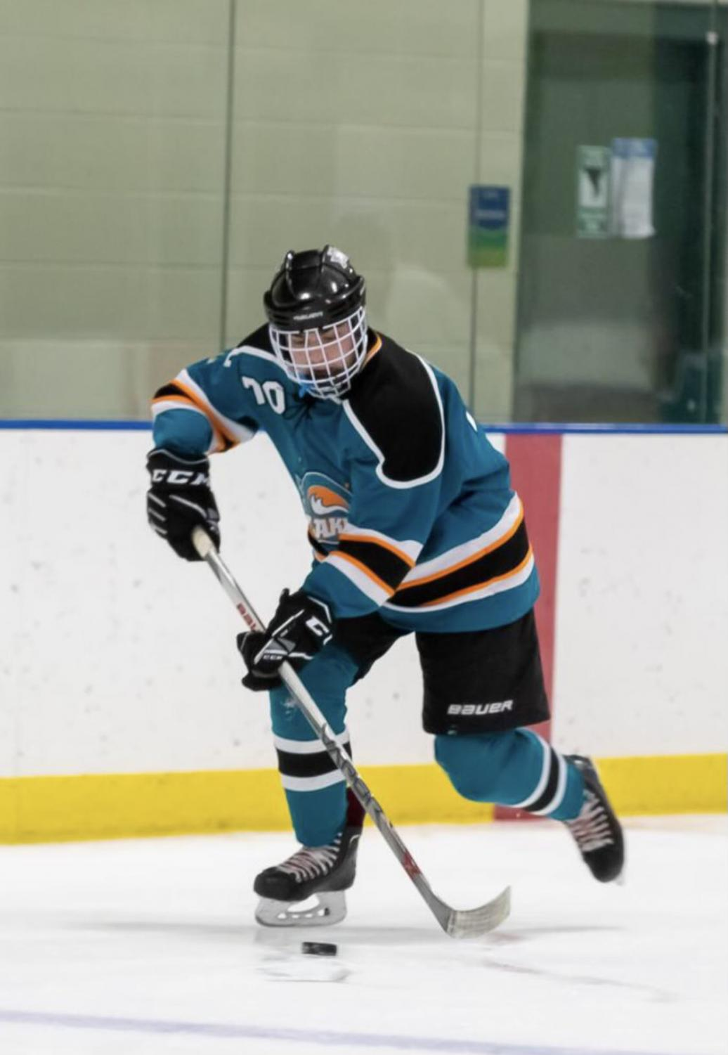 Varsity hockey player Brett Arnopolin takes the puck into offensive position to try and score. Photo Provided by Arnopolin